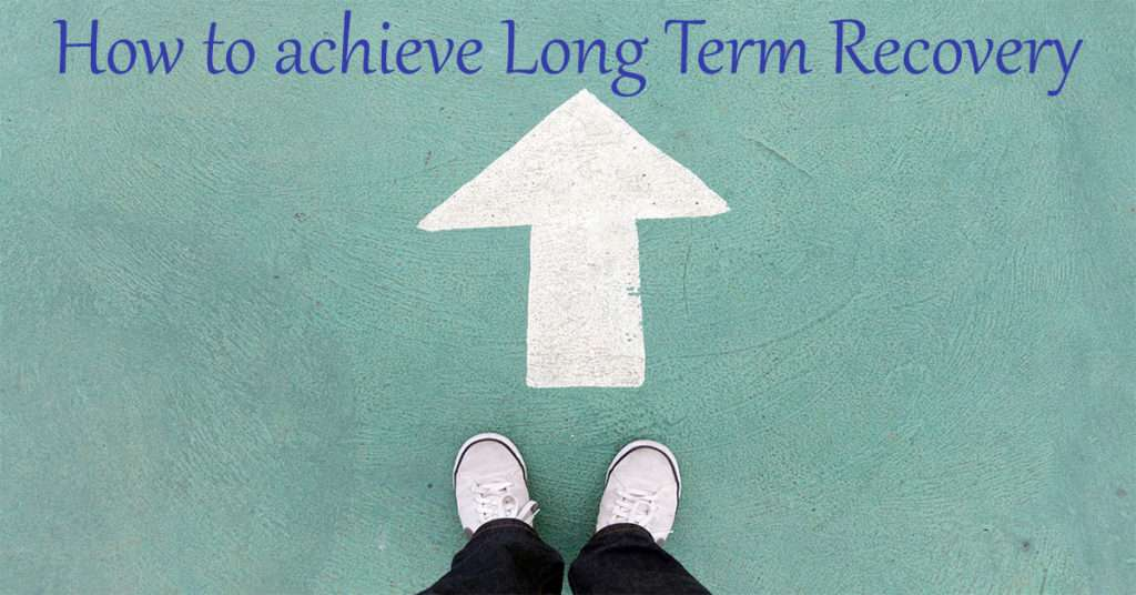 feet standing at an arrow pointing towards a sign that reads how to achieve long term recovery