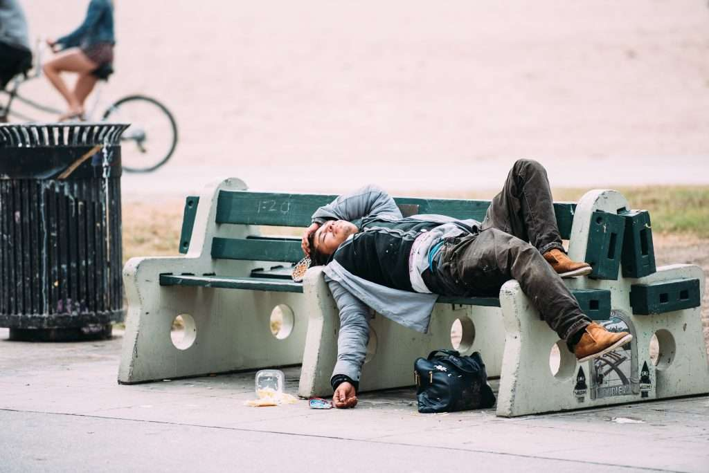 man laying with eyes closed on a public bench